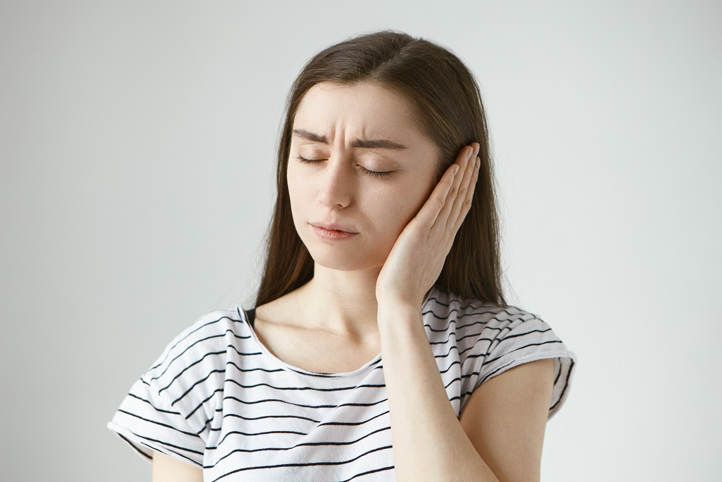 Studio shot of attractive casually dressed young dark haired female keeping eyes closed and covering sore ear with hand while having some problems with hearing. Health, people and pain concept